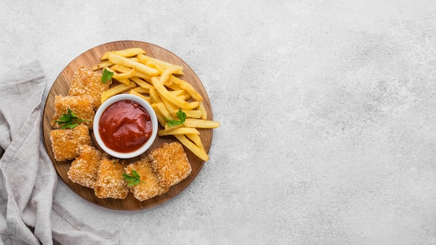 Top view of french fries with fried chicken nuggets and copy space