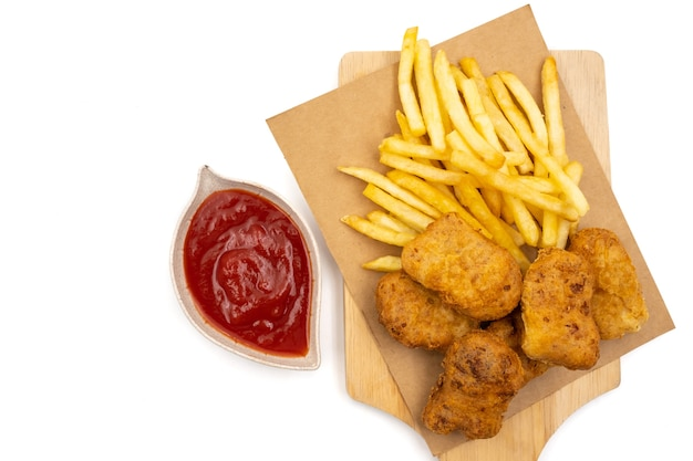 Top view of french fries with nuggets and ketchup on a white background.