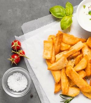 Vista dall'alto di patatine fritte con sale e ciotola di salsa