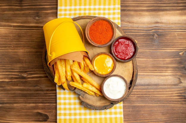 Top view of french fries with seasonings on wooden table