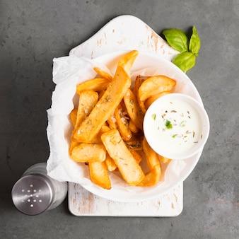 Vista dall'alto di patatine fritte con salsa speciale ed erbe aromatiche