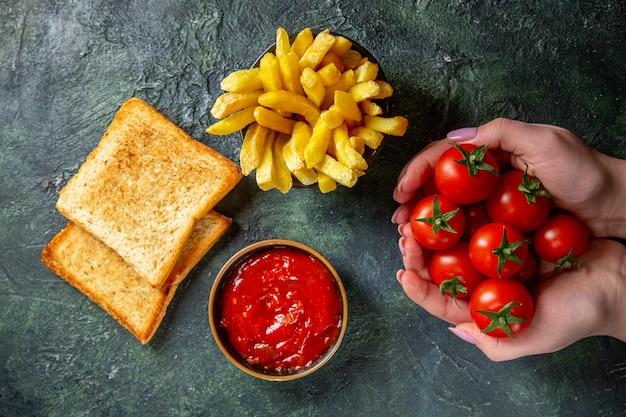 어두운 표면에 여성 손에 토스트와 빨간 체리 토마토와 상위 뷰 감자 튀김