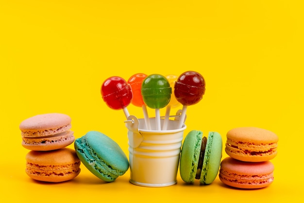 A top view french macarons along with lollipops and colorful candies spread all on yellow, sugar sweet confectionery Free Photo