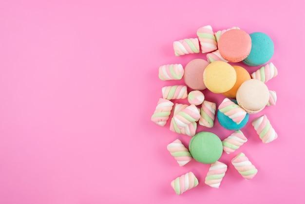 Una vista dall'alto macarons francesi insieme a marshmallow sul colore rosa, zucchero dolce