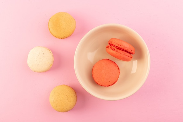 A top view french macarons colored inside and outside plate on the pink table cake biscuit sugar sweet
