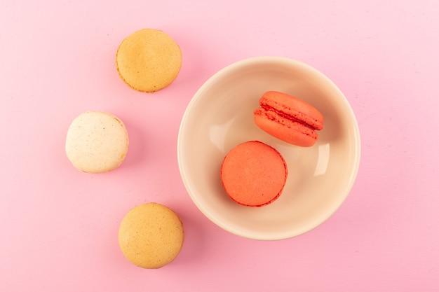 Una vista dall'alto macarons francesi colorati all'interno e al di fuori del piatto sulla tavola rosa torta biscotto zucchero dolce