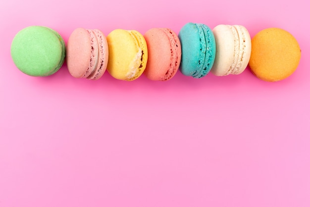A top view french macarons colorful round delicious lined on pink, cake biscuit confectionery
