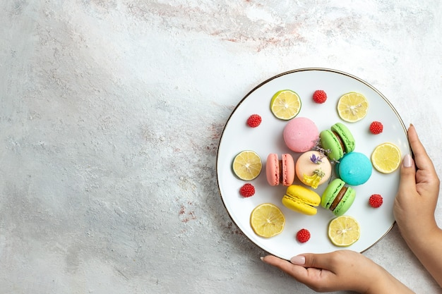 Top view french macarons delicious little cakes with lemon slices on white space