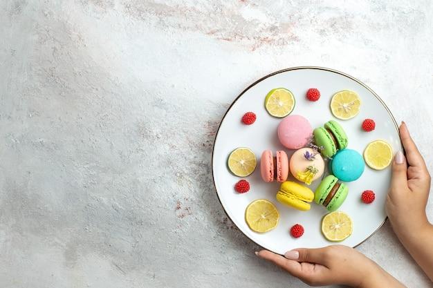 Vista dall'alto macarons francesi deliziose torte con fette di limone su uno spazio bianco