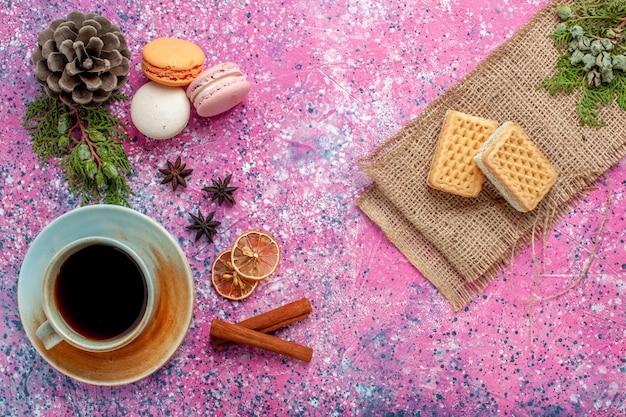 분홍색 표면에 차와 와플이있는 상위 뷰 프랑스 마카롱 맛있는 작은 케이크