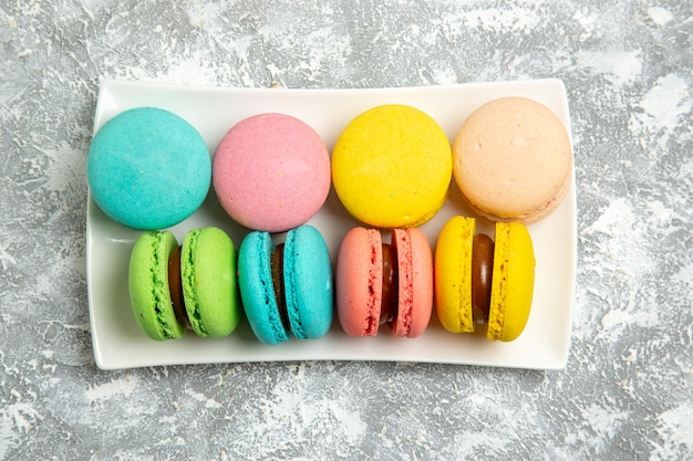 Top view french macarons ful cakes on white surface