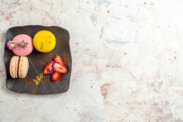 白いテーブルの上のプレートの内側のフランスのマカロンの上面図ビスケットケーキ甘い果物