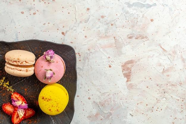 白い床の上のプレートの内側のフランスのマカロンの上面図ビスケットケーキ甘い果物