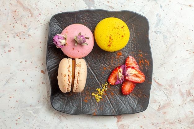 Вид сверху французские макароны внутри тарелки на белом столе, бисквитный торт, сладкие фрукты