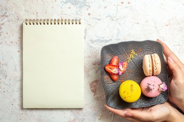 Macarons francesi di vista superiore all'interno del piatto sulla torta dolce del biscotto del biscotto della scrivania bianca