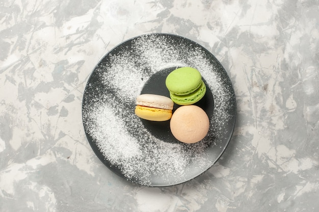 Top view french macarons inside plate on white surface cake sugar bake biscuit sweet tea cookie