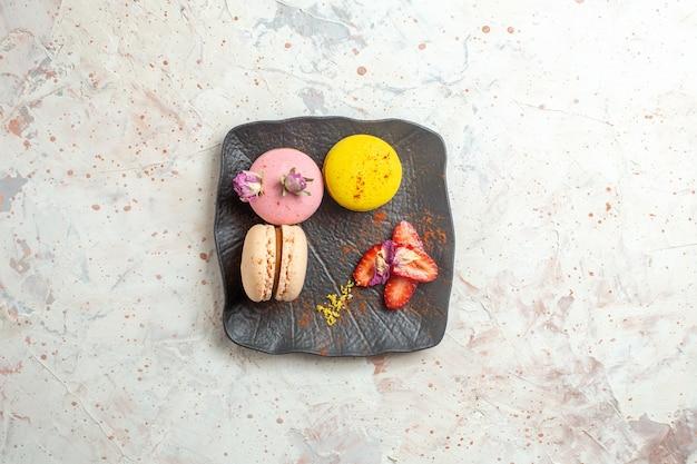Macarons francesi di vista superiore all'interno del piatto sulla frutta dolce della torta del biscotto della tavola bianca