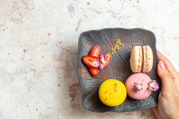 Top view french macarons inside plate on a white table cookie biscuit sweet cake