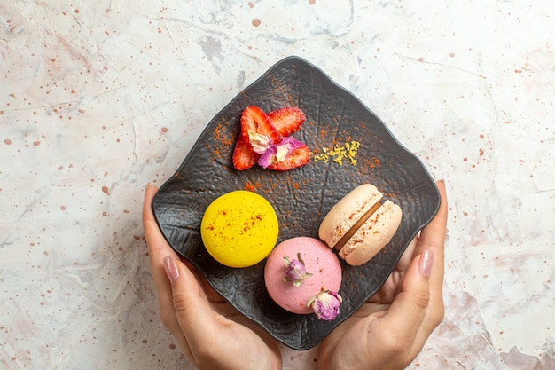 Top view french macarons inside plate on the white table cookie biscuit sweet cake