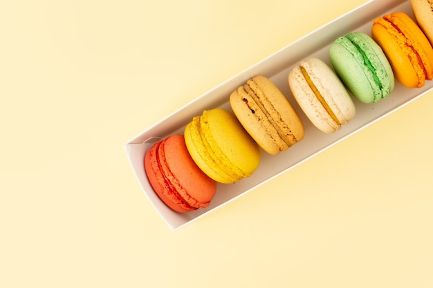 A top view french macarons lined on the yellow table cake biscuit sugar sweet