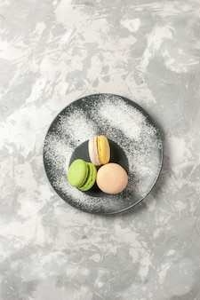 Вид сверху французские макароны маленькие вкусные пирожные на белой поверхности бисквитный сахарный торт сладкий пирог чайное печенье