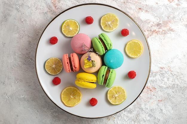 Vista dall'alto macarons francesi piccole torte deliziose con fette di limone su una superficie bianca torta biscotto zucchero biscotto dolce