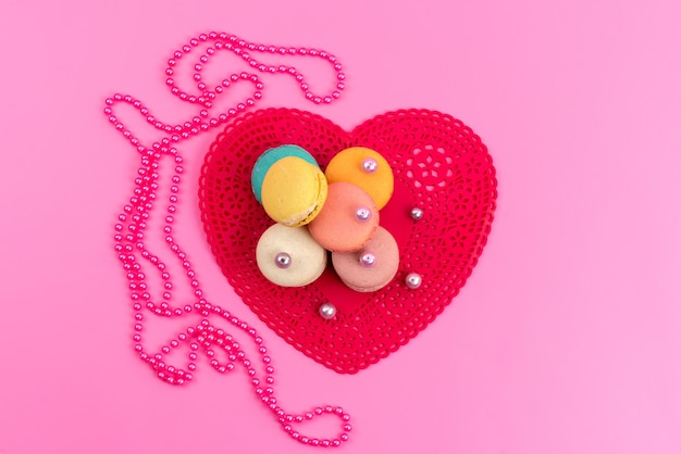 A top view french macarons round delicious along with red heart shaped form on pink, cake biscuit sweet