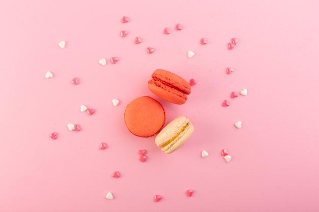 Una vista dall'alto macarons francesi rotondi e squisiti sullo zucchero rosa del biscotto della torta della tavola dolce