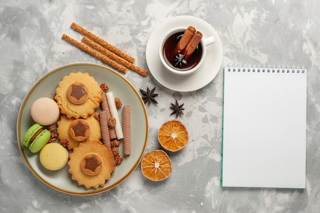 Vista dall'alto macarons francesi con torte tè e biscotti sulla superficie bianca biscotto biscotto zucchero cuocere torta torta dolce