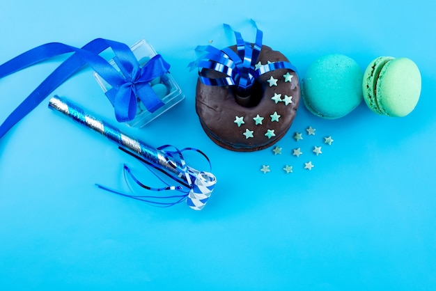 A top view french macarons with chocolate donuts and party decorations on blue, candy bsicuit cake color