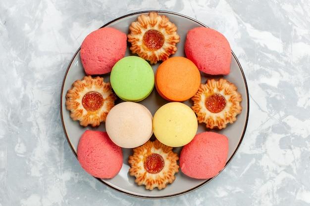 Macarons francesi vista dall'alto con biscotti su superficie bianca chiara