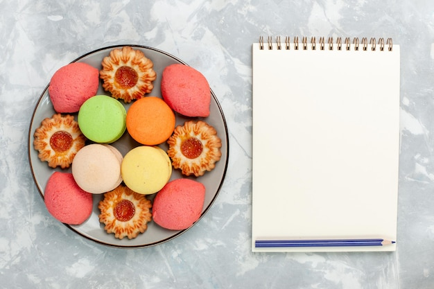 Top view french macarons with cookies and notepad on light-white surface