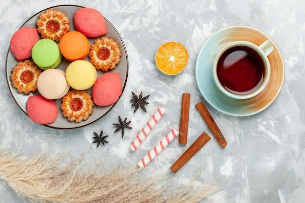 Macarons francesi vista dall'alto con biscotti e tè su una superficie bianca chiara