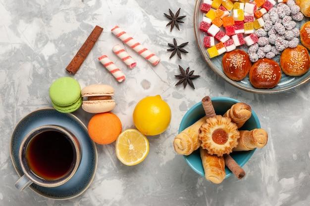 Vista dall'alto macarons francesi con una tazza di ciambelle di tè e piccoli panini dolci sulla superficie bianca
