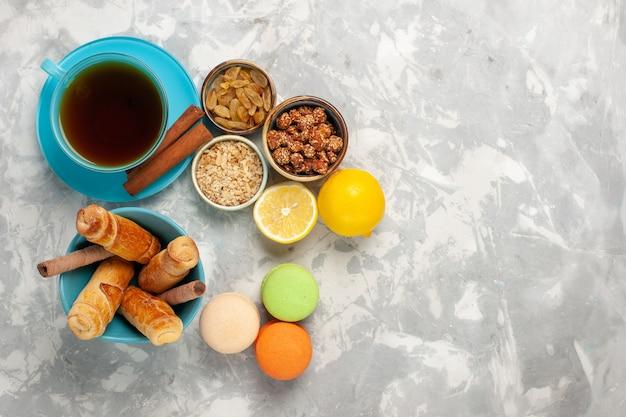 Vista dall'alto macarons francesi con una tazza di ciambelle di tè sulla superficie bianca