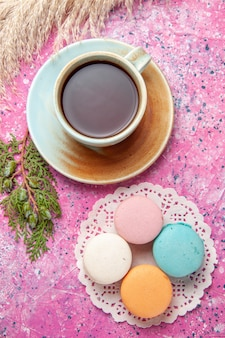 Top view of french macarons with cup of tea on pink surface