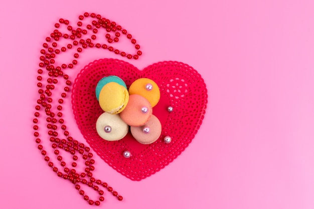 A top view french macarons with heart shaped red form on pink, cake biscuit confectionery