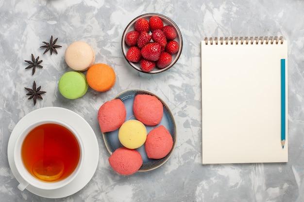 Вид сверху французские макароны с маленькими пирожными и чашкой чая на белой поверхности торт бисквитный сахар сладкий пирог чай