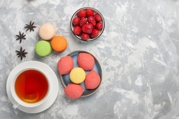 Top view french macarons with little cakes and cup of tea on white surface cake biscuit sugar sweet pie tea
