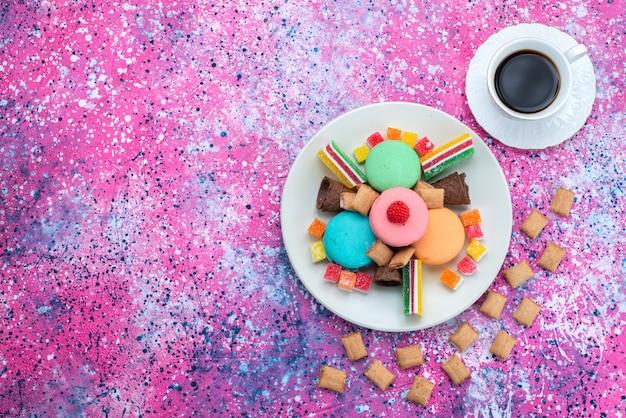 Вид сверху французские макароны с мармеладом вместе с чашкой кофе на красочном фоне торт бисквитное цветное фото