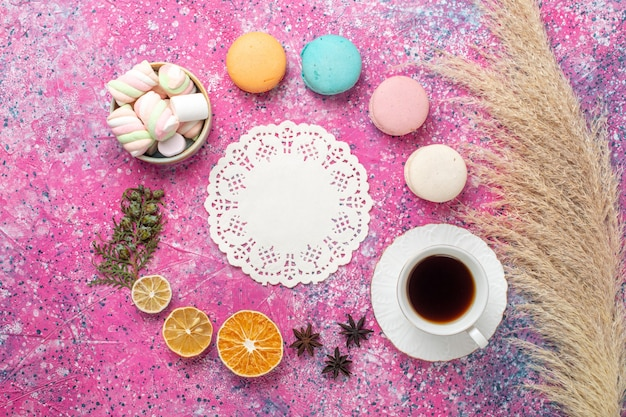 Top view of french macarons with marshmallows and cup of tea on pink surface