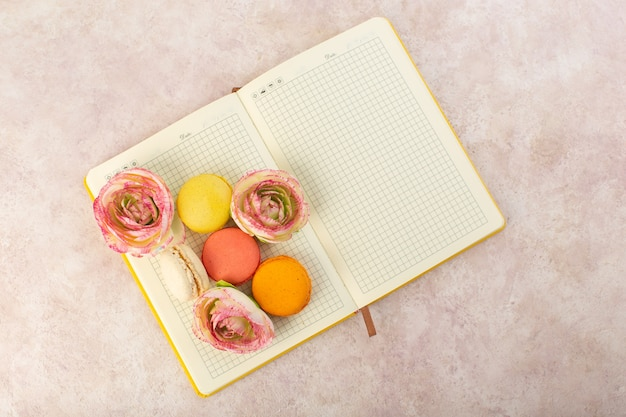 A top view french macarons with roses on the copybook and pink table cake biscuit sugar sweet