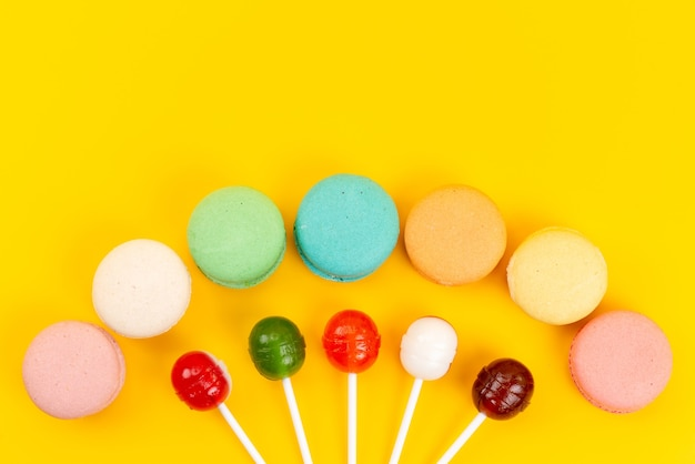 A top view french macarons with sweet and sour lollipops on yellow, cake biscuit bake
