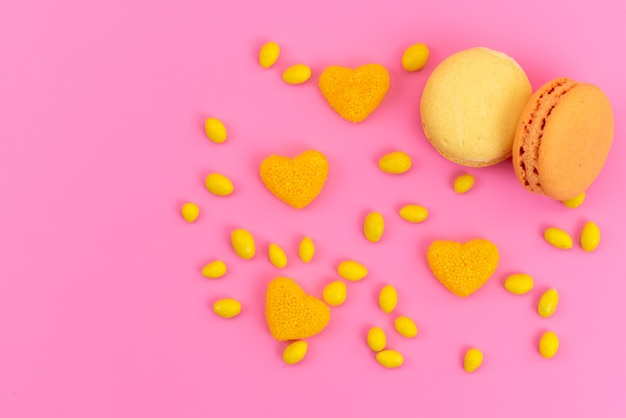 A top view french macarons with yellow, candies on pink, cake biscuit color