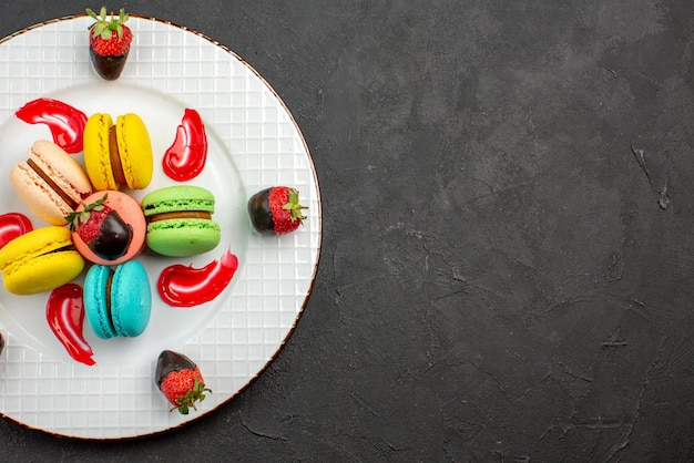暗いテーブルの上のチョコレートで覆われたイチゴとフランスのマカロンを食欲をそそるフランスのマカロンの上面図