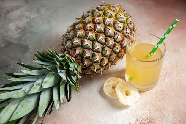 ベージュの背景にジュースガラスピペットドライアナナスリングを置く新鮮なアナナスの上面図