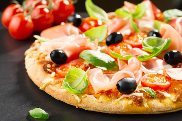 Top view of fresh appetizing pizza on dark