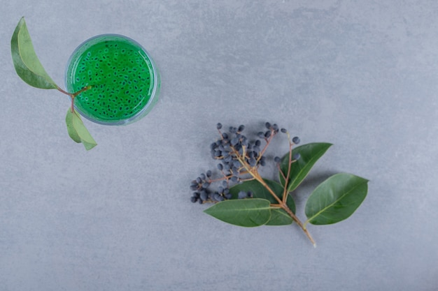 Top view of fresh apple juice in green leaves over grey surface
