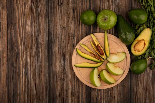 Vista dall'alto di fette di mela fresca su una tavola di cucina in legno con fette di avocado con mele intere lime di avocado e prezzemolo isolato su una superficie di legno con spazio di copia