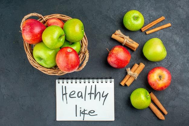 Вид сверху свежие яблоки в плетеной корзине палочки корицы здоровый образ жизни, написанные в блокноте на темной поверхности
